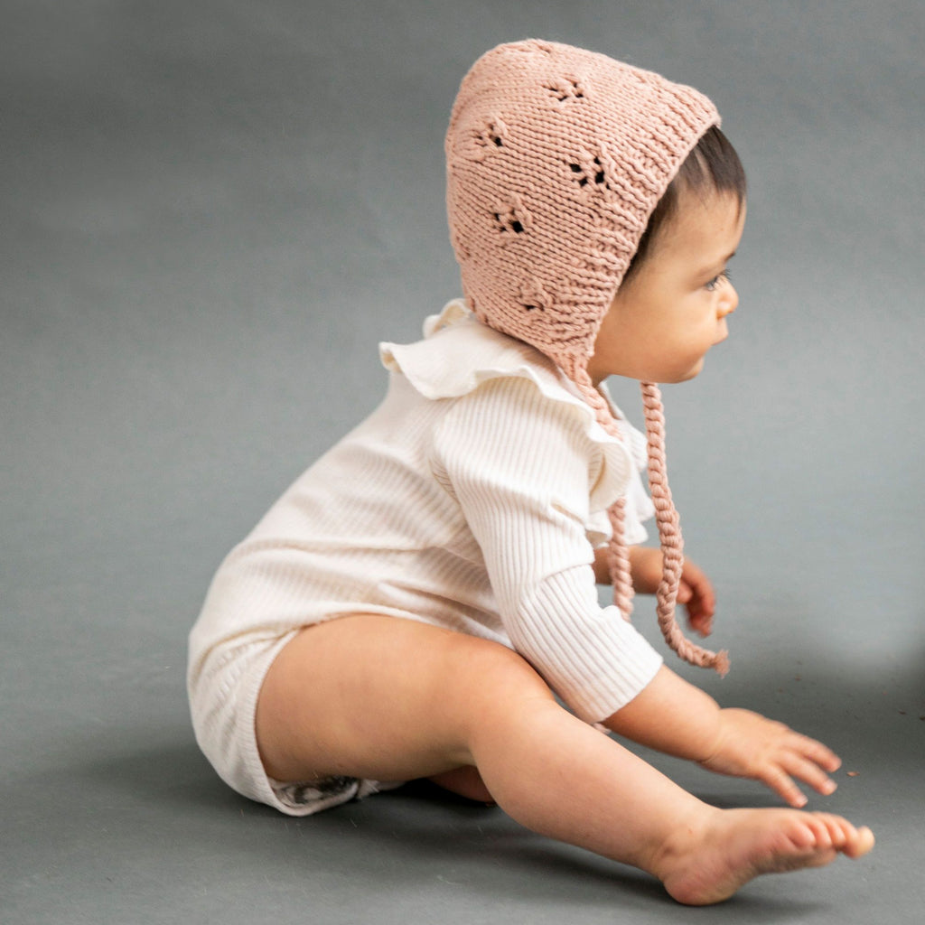 hand knit dusty pink cotton bonnet with openwork stitching and tie closure