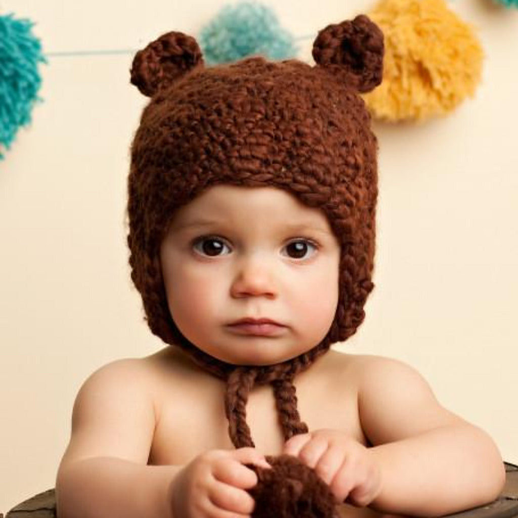 crochet bear hat with ears and pom tassels for baby and toddler brown