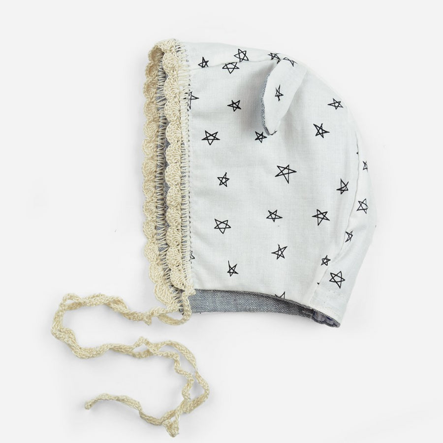 reversible cotton bonnet for babies in chambray and crochet trim and ears with White and black spot print fabric