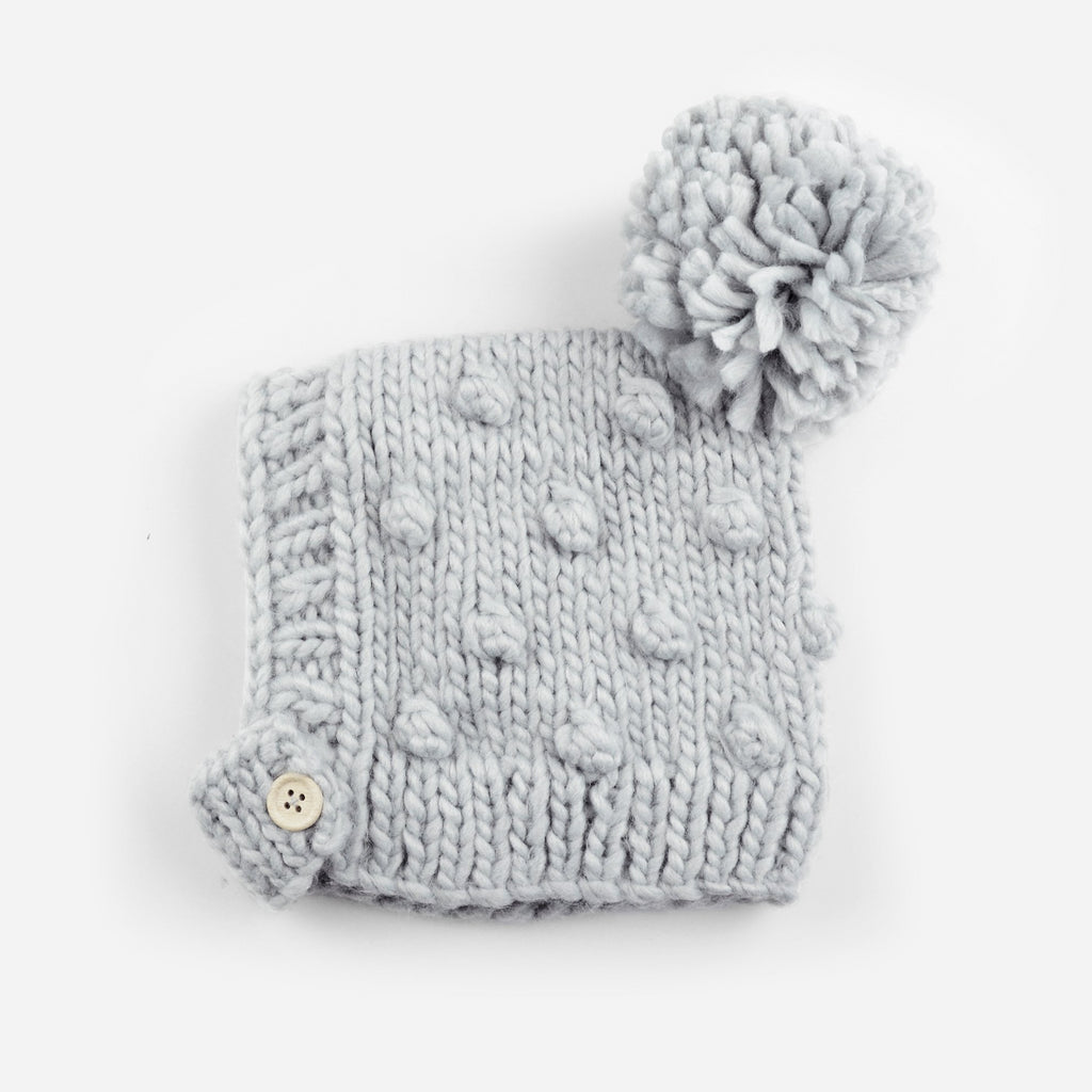 hand knit gray bonnet with popcorn knit pattern and pom, wood button closure