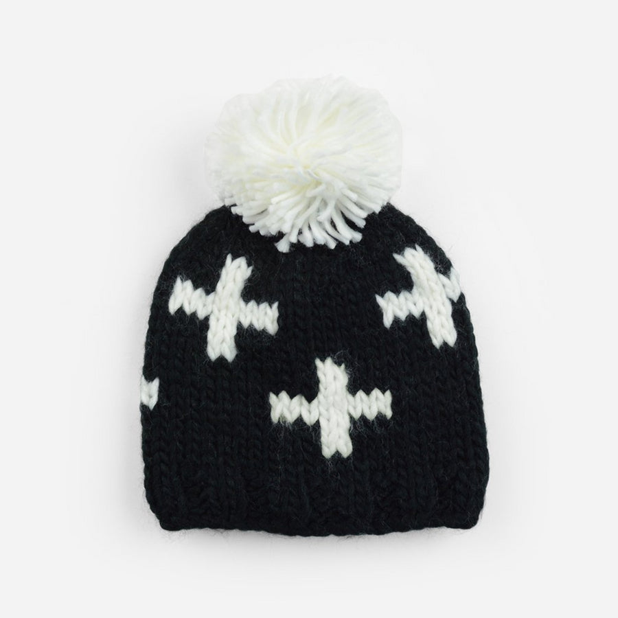 black hand knit beanie with white pom and and swiss cross pattern