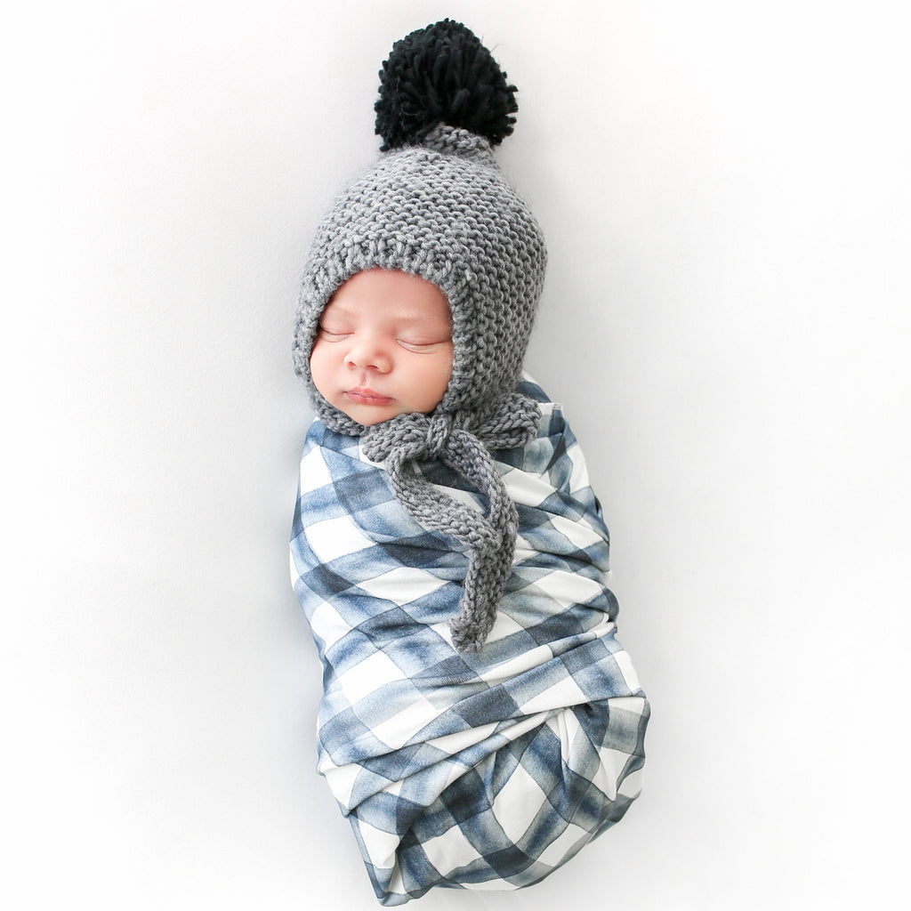 gray hand knit bonnet for baby and toddler with tie closure and black yarn pom