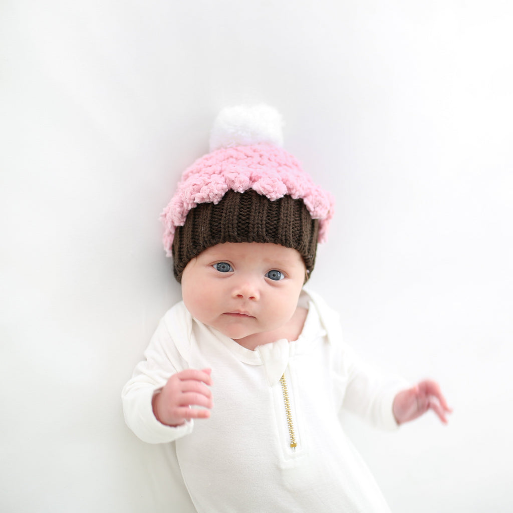 hand knit acrylic and chenile yarn cupcake hat in brown with pink and white pom accent for baby infant toddler child birthday smash cake