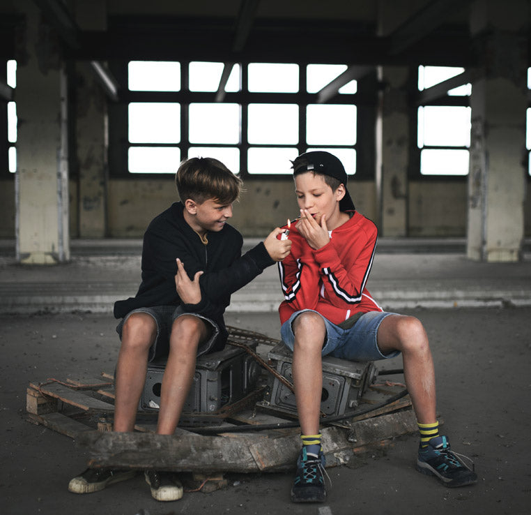 young teenage boys smoking a cigarette in an abandoned warehouse