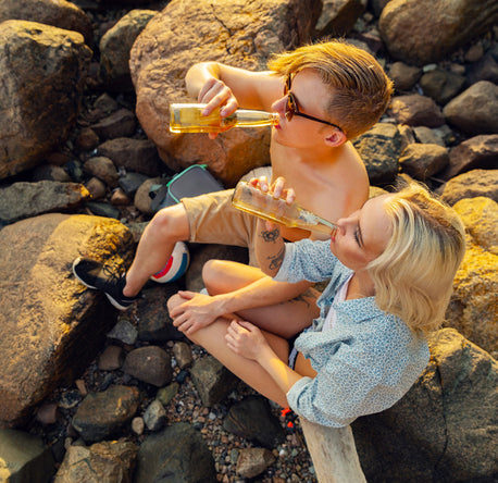 couple drinking on rocks at the beach