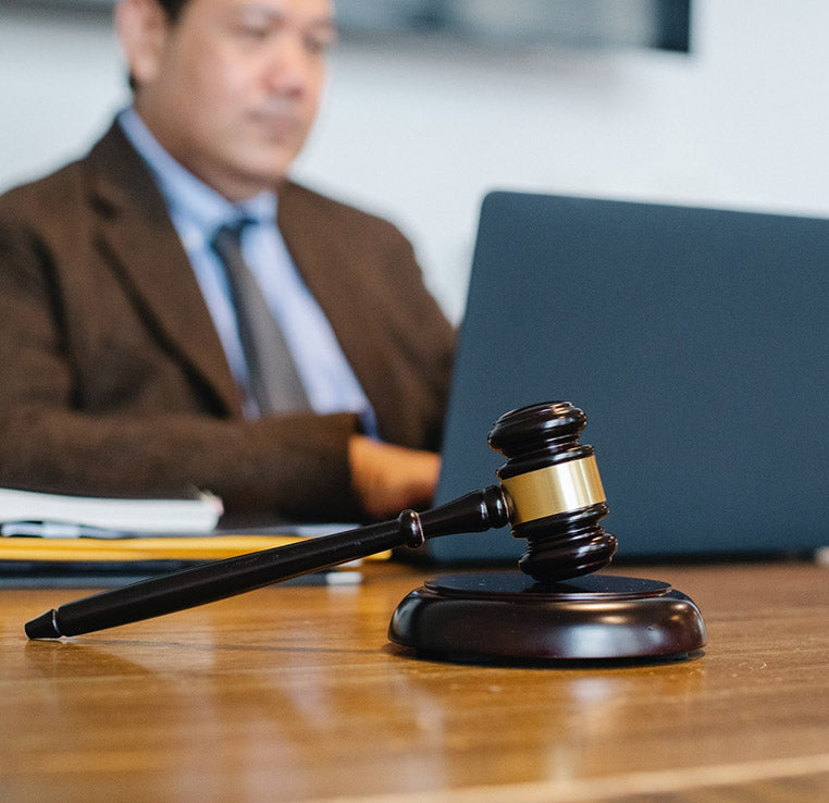 Gavel with man on computer in the back