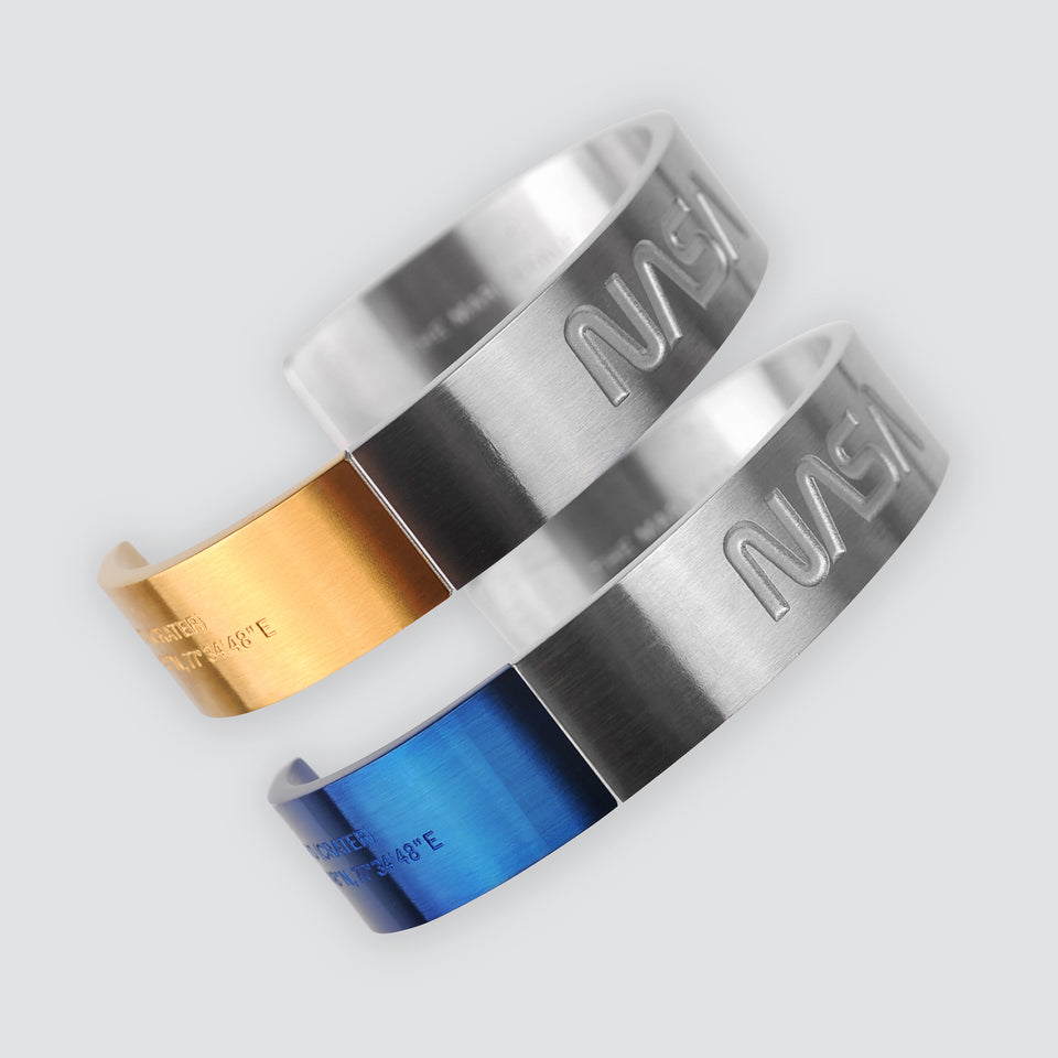 Futuristic elegance. A slip-on gold/silver or blue/silver duo-colored stainless steel bracelet with the landing coordinates and NASA logo embossed. A collaboration with Shannnam.