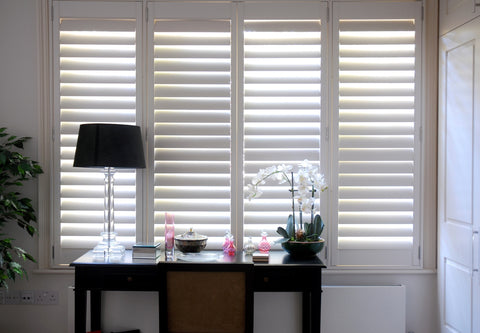 the light is gently seeping through half closed mdf shutters with no visible tilt rod