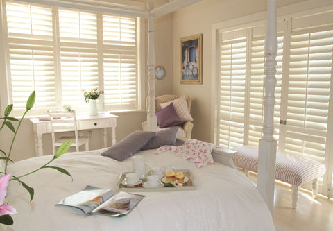 hardwood white shutters on both windows of a large bedroom. the pastel white coloured shutters allows the control of the amount of light