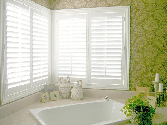 white plantation shutters mounted on a corner window in a bathroom letting a lot of light through but still assuring privacy