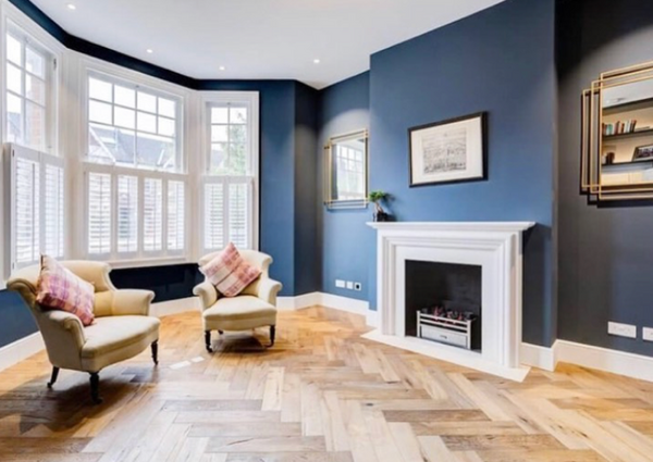 large living room with fire place, blue wall and bay window with shutters