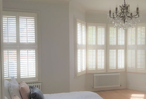 shutter materials: hardwood shutters mounted on both windows of a large bedroom. the half open louvres letting the light through the shutters