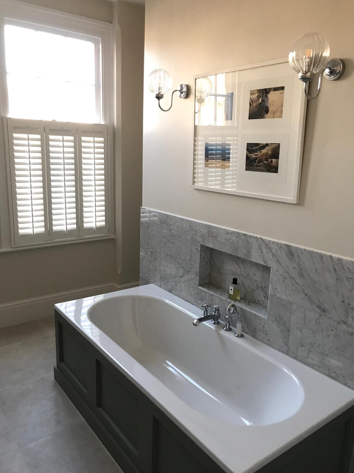 white cafe style bathroom shutters over a bathtub