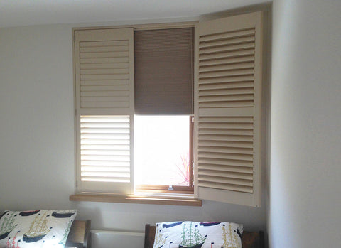 half open shutters with darkening blind half lowered