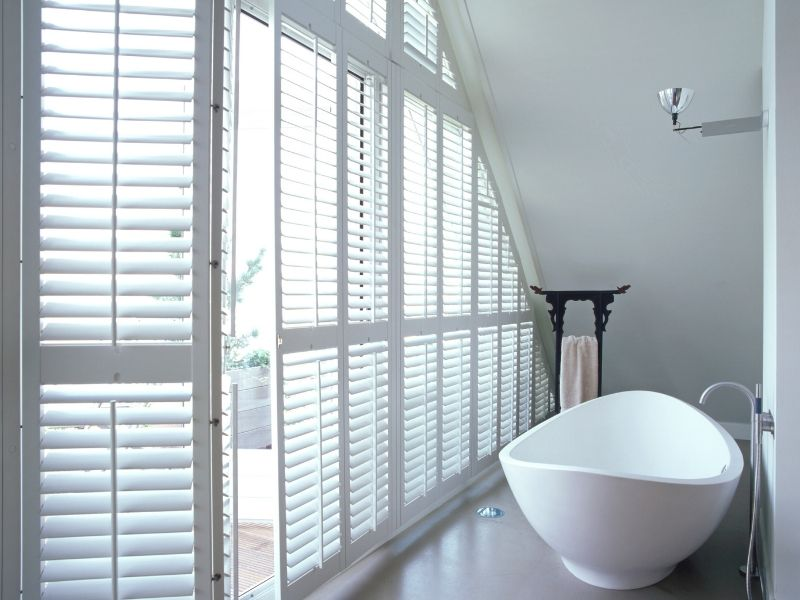 custom made shutters for a bathroom with a modern bath tub and a very large shaped window