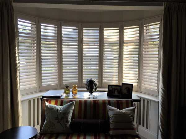 half closed shutters on a bay window letting only a little light through the window