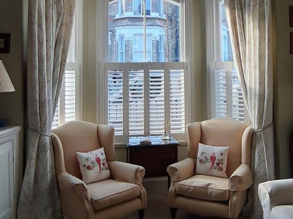 window with shutters and curtains with two armchairs in front