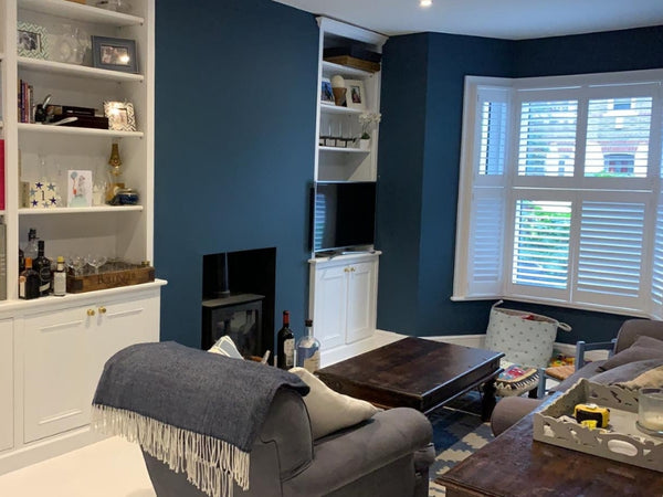 white bay window shutters in a living room in west london