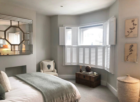 large bedroom with bay window and tier on tier shutters half open