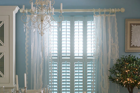 elegant room with window letting light in through plantation shutters