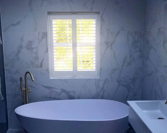 small shutters in a bathroom with stylish bath tub