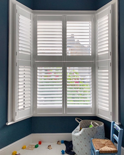 detail of white shutters on a bay window in a property in West London