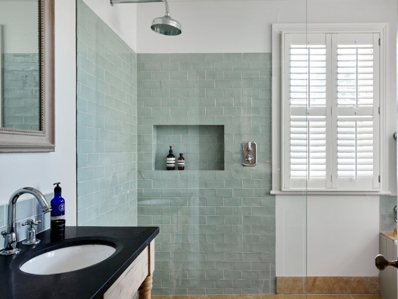 bathroom with shower and shutters on the window