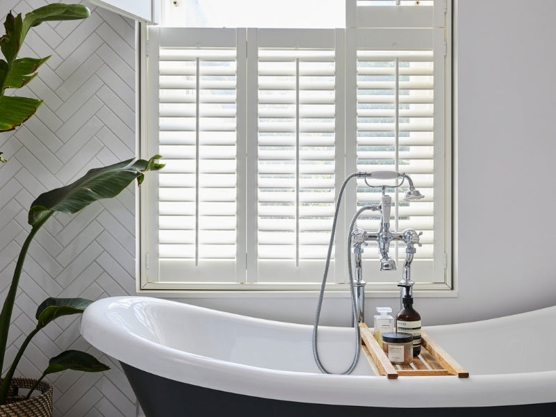 traditional bathtub and shutters on the window
