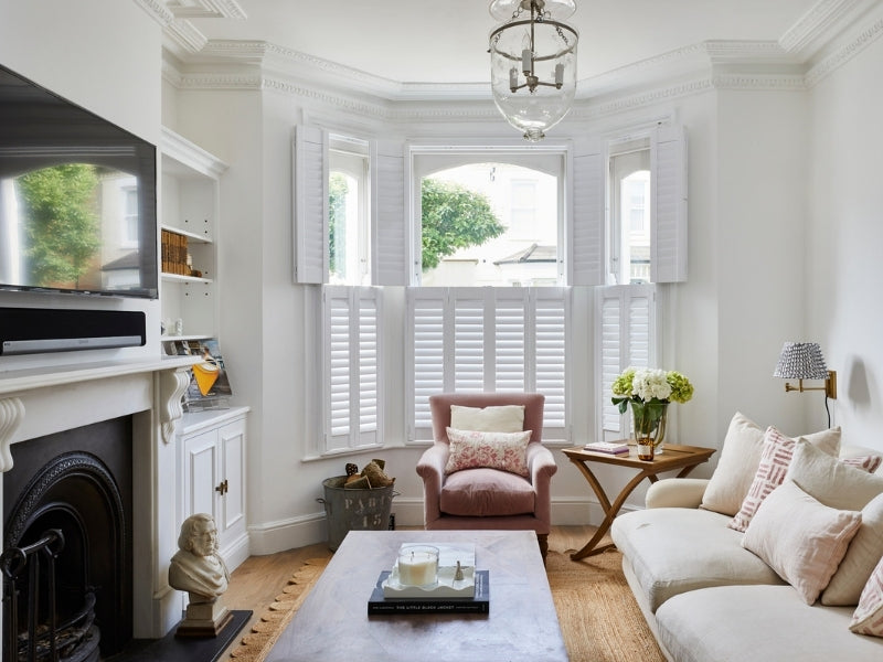 tier on tier shutters in a lounge with chimney and white sofe