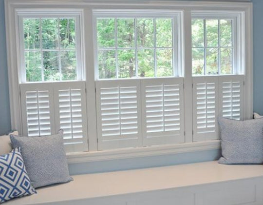 cafe style plantation shutters with matching cushions and seat under the window