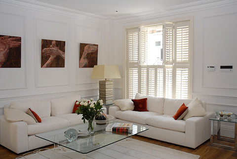 white lounge, corner sofa and half open tier on tier basswood shutters