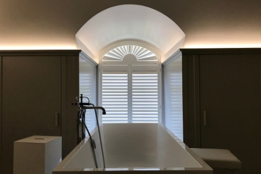 dark bathroom with modern bath tub and white shutters on the arched window