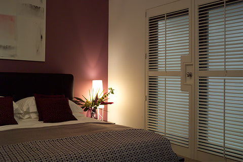 dark bedroom with closed wooden shutters