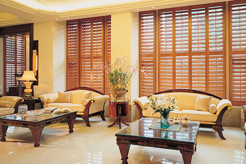large room with tall windows covered with coloured wooden shutters