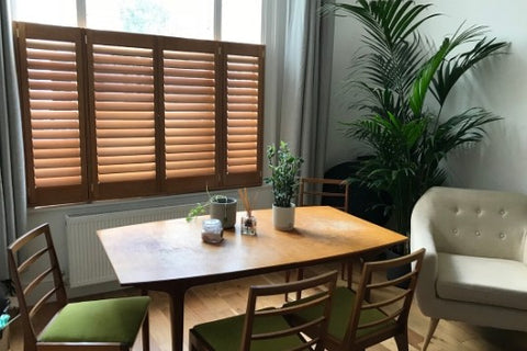 room with table and chairs and window with coloured wooden shutters in cafe style