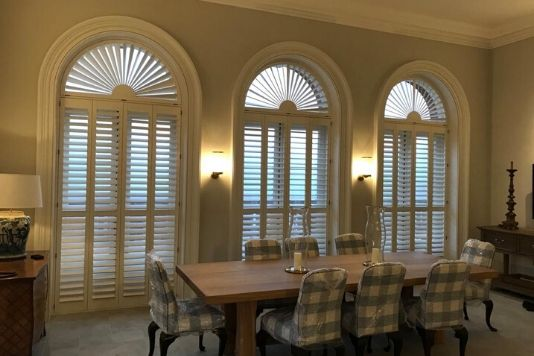 dining room with arched windows and wooden shutters letting a little light through