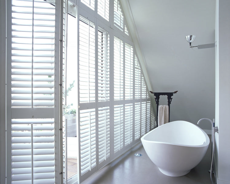 bathroom with sloping ceiling and large window with plantation style shaped shutters