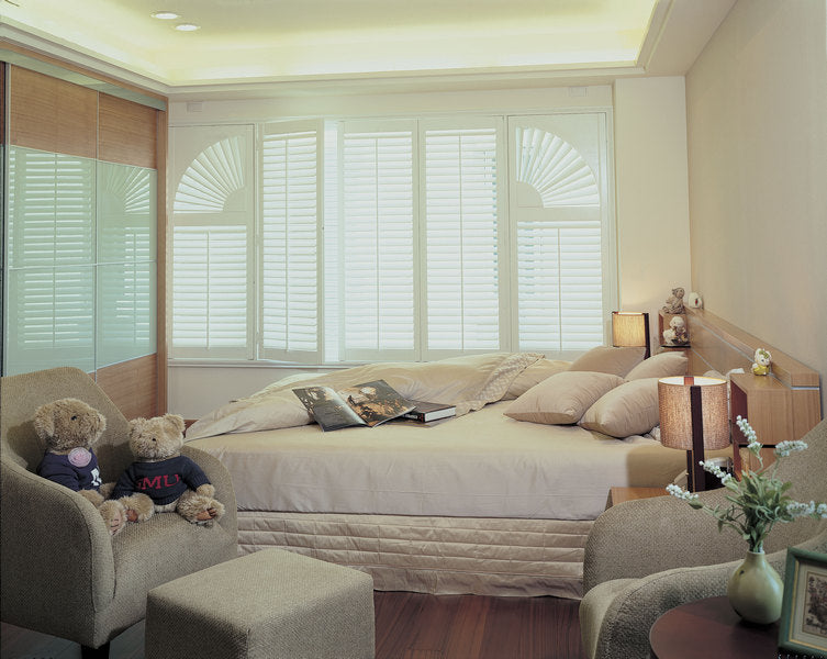 double bedroom illuminated through window shutters in a special curved shape
