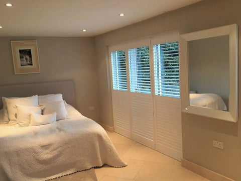modern bedroom with large window with full height shutters, louvres half open to let the light in form the top
