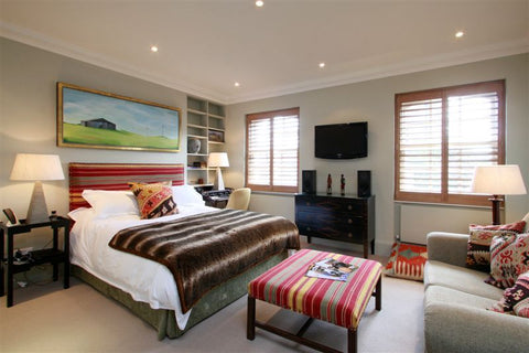 large double bedroom with coloured decoration and stained shutters on the bedroom window