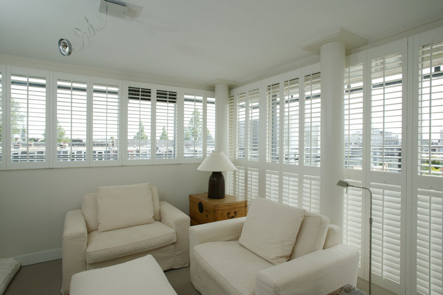 fully illuminated modern living room dominated by white colours, with white shutters on the windows