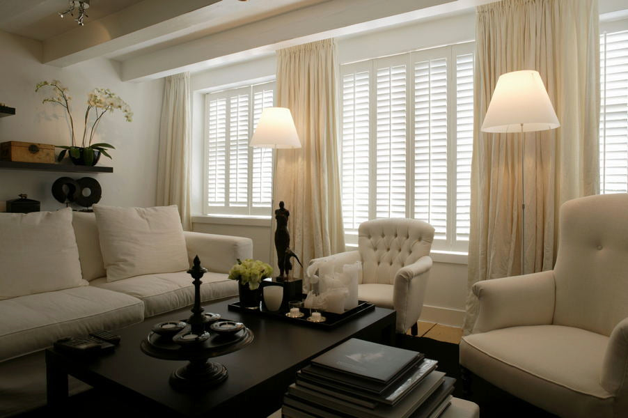 elegant living room in pastel colour with white sofas, white shutters and cream curtains