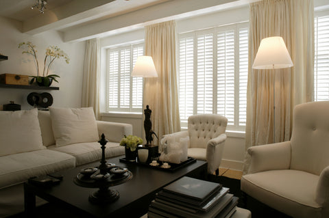 elegant living room with white sofas lamps near the windows and shutters