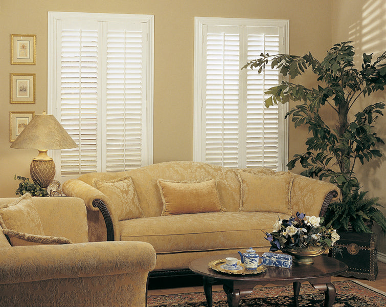full height shutters in a living room behind a old style sofa
