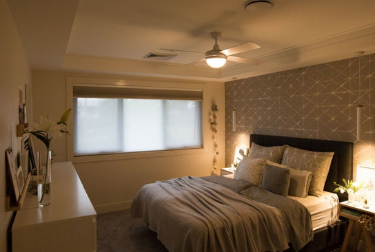 double bedroom slightly lit with honeycomb blinds on the only window