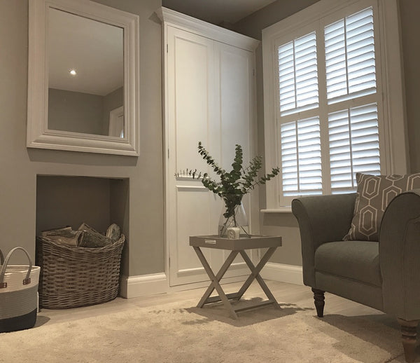 image of an interior design development detail showing a grey colour palette for walls, sofa and white door and interior shutters