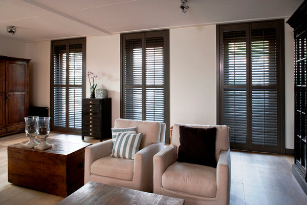 stylish lounge with elegant armchairs and dark plantation shutters on the three windows in the background