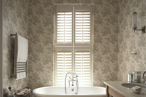 bathroom window treatment with dark shutter matching the wall paper window behind an oval shaped bathtub