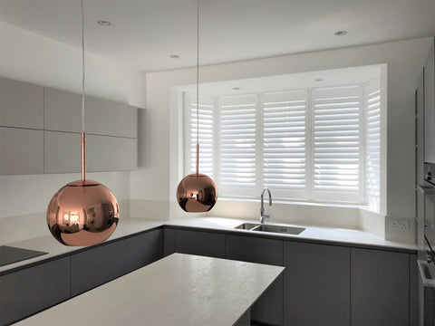 modern kitchen with large copper lamp and white abs shutters on the window behind the sink