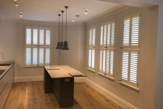 large kitchen with central wooden table and white tier on tier shutters on the window